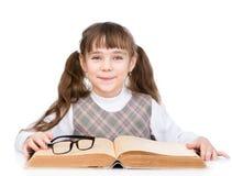 Piccola scolara con il grande libro Isolato su priorità bassa bianca Fotografie Stock Libere da Diritti