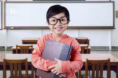 Piccola scolara con un libro nella classe Immagine Stock