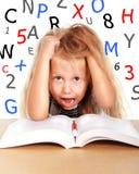 Piccola scolara dolce che tira i suoi capelli biondi nello sforzo con i numeri e le lettere Immagine Stock