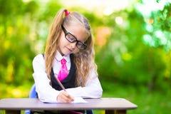 Piccola scolara sveglia con le note e le matite Fotografia Stock Libera da Diritti