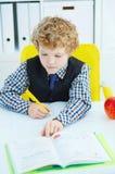 Piccola scrittura caucasica dello scolaro in un taccuino che si siede ad una tavola La mela rossa si trova accanto alla tavola Immagini Stock Libere da Diritti