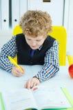 Piccola scrittura caucasica dello scolaro in un taccuino che si siede ad una tavola La mela rossa si trova accanto alla tavola Fotografie Stock Libere da Diritti