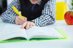 Piccola scrittura caucasica dello scolaro in un taccuino che si siede ad una tavola La mela rossa si trova accanto alla tavola Te Immagini Stock