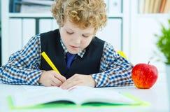 Piccola scrittura caucasica dello scolaro in un taccuino che si siede ad una tavola La mela rossa si trova accanto alla tavola Te Fotografie Stock