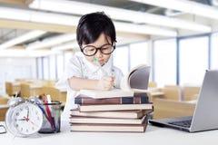 Piccola scrittura della ragazza sul libro nella classe Immagine Stock Libera da Diritti