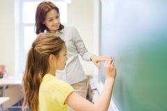 Piccola scrittura sorridente della scolara sul bordo di gesso Immagini Stock