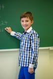 Piccola scrittura sorridente dello scolaro sul bordo di gesso Fotografie Stock Libere da Diritti