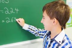 Piccola scrittura sorridente dello scolaro sul bordo di gesso Immagine Stock