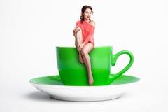 Piccola seduta femminile sulla tazza di caffè gigante; donna sulla dieta, Immagine Stock Libera da Diritti