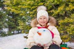 Piccola seduta sveglia della ragazza e la testa del pupazzo di neve della tenuta Fotografia Stock