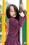 Piccola signora asiatica su un campo da giuoco Fotografia Stock Libera da Diritti