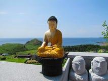 Piccola statua di Buddha che indossa i vestiti gialli e con una moneta d'argento sulla mano sinistra immagini stock