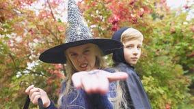 Piccola strega che mostra il ragno del giocattolo nella macchina fotografica, arachnophobia, timore su Halloween stock footage