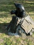 Piccola talpa della scultura bronzea del parco, guardante fuori dal foro di pietra Fotografia Stock