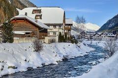 Piccola torrente montano nelle alpi del Tirolo La casa di legno vicino al fiume della montagna è coperta da neve Immagine Stock