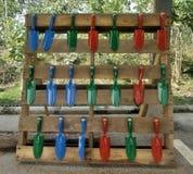 Piccola vanga di giardinaggio colourful sulla ferrovia di legno nel giardino del cortile Immagini Stock Libere da Diritti
