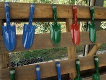 Piccola vanga di giardinaggio colourful sulla ferrovia di legno nel giardino del cortile Fotografia Stock