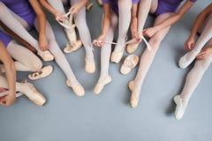 Piccole ballerine che mettono sulle scarpe, immagine potata Fotografie Stock Libere da Diritti