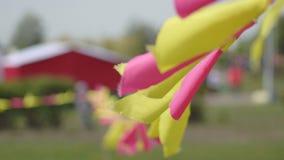 Piccole bandiere festive multicolori rosse ed ondeggiamento giallo e fluttuare nel vento, decorazione, fondo stock footage