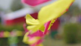 Piccole bandiere festive multicolori rosse ed ondeggiamento giallo e fluttuare nel vento, decorazione, fondo, lento archivi video
