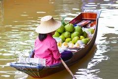 Piccole barche di galleggiamento della Tailandia, del mercato caricate con la frutta e le verdure colourful e remate dalle donne  immagini stock
