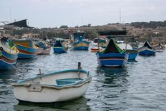 Piccole barche in Marsaxlokk in un giorno nuvoloso fotografia stock libera da diritti