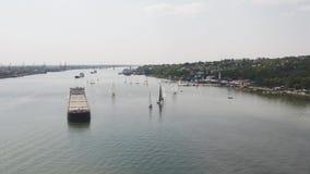 Piccole barche a vela nello stretto con una grande autocisterna Barche a vela e un'autocisterna video d archivio