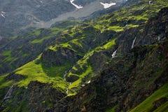 Piccole cascate sulle colline verdi di estate in valle delle alpi Fotografia Stock