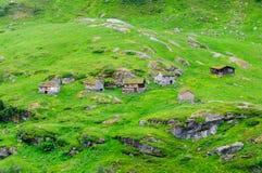 Piccole case del villaggio alla valle verde Immagini Stock