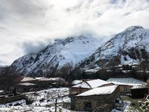 Piccole case di pietra, costruzioni nel villaggio su una localit? di soggiorno fredda di inverno della bella montagna con la fosc fotografie stock