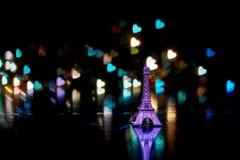 Piccole chiavi della siluetta miniatura della torre Eiffel sui portachiavi a anello con una riflessione sul bokeh sotto forma di  Fotografia Stock