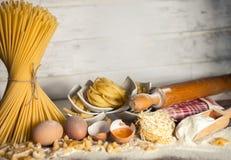 Piccole ciotole con pasta con il matterello, gli spaghetti legati e la farina Fotografia Stock Libera da Diritti