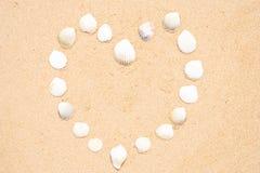 Piccole conchiglie sotto forma di un cuore su una spiaggia sabbiosa liscia immagine stock libera da diritti