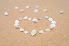 Piccole conchiglie sotto forma di un cuore su una spiaggia sabbiosa liscia fotografia stock