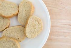 Piccole fette di pane francese su un piatto bianco Fotografia Stock