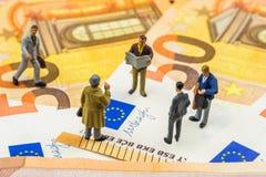 Piccole figurine che discutono e che stanno sulla nuova banconota dell'euro 50 Fotografia Stock Libera da Diritti