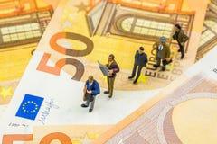 Piccole figurine che stanno nella linea sulle nuove 50 euro banconote Fotografie Stock