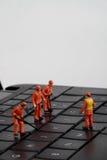 Piccole figurine dei lavoratori che riparano la tastiera di computer Immagini Stock Libere da Diritti