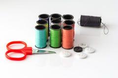 Piccole forbici e primo piano multicolore del fondo dei filati cucirini Immagini Stock