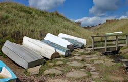 Piccole imbarcazioni a remi rovesciate da un piccolo ponte dalla costa a Eype in Dorset immagine stock libera da diritti