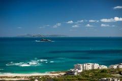 Piccole isole pietrose nel mare azzurrato con la priorità alta delle case e della spiaggia Fotografia Stock Libera da Diritti
