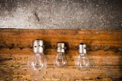 Piccole, lampadine medie e grandi sui chiodi sul vecchio di legno Fotografie Stock