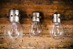 Piccole, lampadine medie e grandi sui chiodi sulla vecchia fine di legno su Immagine Stock