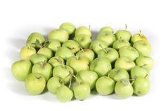 Piccole mele verdi su bianco Fotografia Stock