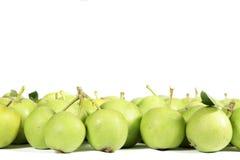 Piccole mele verdi su bianco, con spazio libero da scrivere sulla cima Fotografia Stock