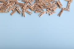 Piccole mollette di legno sveglie su un fondo blu Fotografia Stock Libera da Diritti
