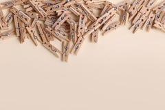Piccole mollette di legno sveglie su un fondo crema Immagine Stock Libera da Diritti