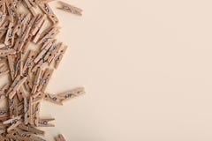 Piccole mollette di legno sveglie su un fondo crema Immagine Stock