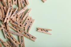 Piccole mollette di legno sveglie su un fondo verde Immagini Stock Libere da Diritti