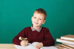 Piccole note sorridenti di scrittura dello scolaro nella classe contro il wa verde Fotografia Stock